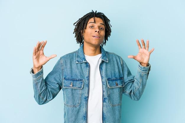 Giovane uomo di colore che indossa una giacca di jeans che tiene qualcosa di poco con gli indici, sorridente e fiducioso.