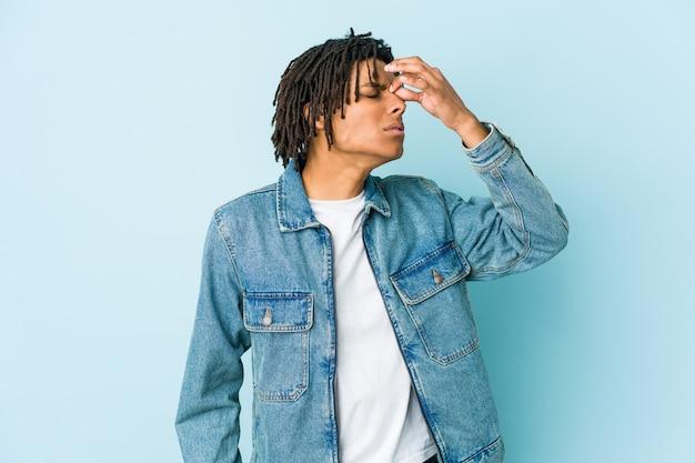 Giovane uomo di colore che indossa una giacca di jeans con mal di testa, toccando la parte anteriore del viso.