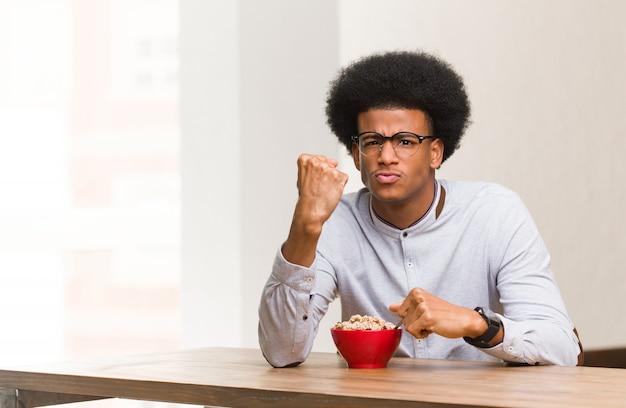 Giovane uomo di colore che mangia una prima colazione che mostra pugno alla fronte, espressione arrabbiata