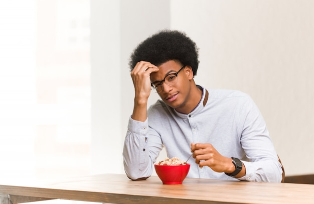 Giovane uomo di colore che mangia una prima colazione preoccupato e sopraffatto