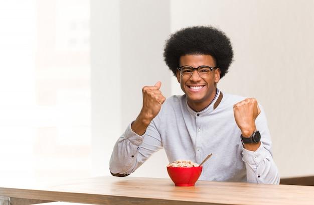 Giovane uomo di colore che mangia una prima colazione sorpreso e scioccato