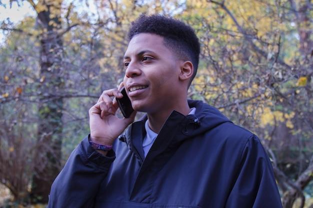 Giovane uomo di colore che parla sullo smart phone nella foresta.