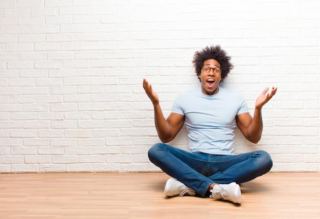 Giovane uomo di colore che si sente felice, eccitato, sorpreso o scioccato, sorridente e stupito di qualcosa di incredibile seduto sul pavimento di casa
