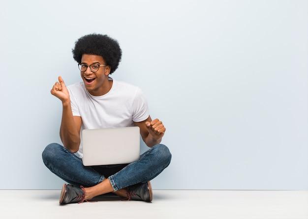 Giovane uomo di colore che si siede sul pavimento con un computer portatile che balla e che si diverte