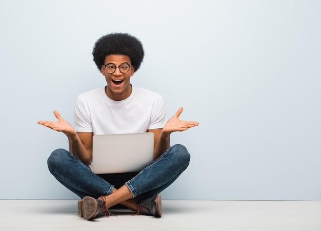 Giovane uomo di colore che si siede sul pavimento con un computer portatile che celebra una vittoria o un successo