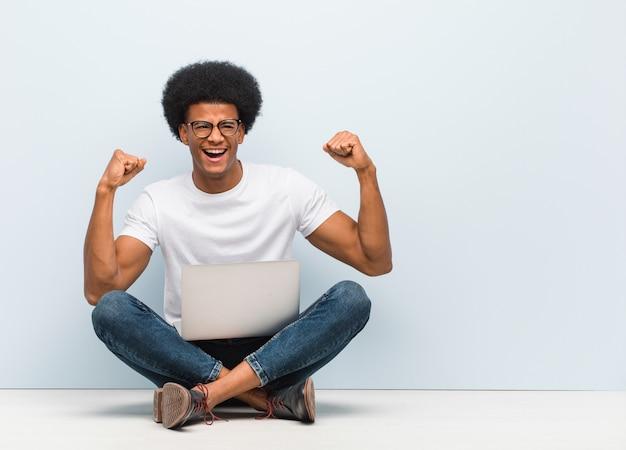 Giovane uomo di colore che si siede sul pavimento con un computer portatile che non si arrende