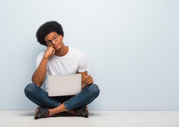 Giovane uomo di colore che si siede sul pavimento con un computer portatile che pensa a qualcosa, guardando al lato