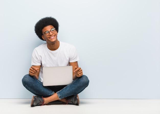 Giovane uomo di colore che si siede sul pavimento con un computer portatile che sogna di raggiungimento degli scopi e degli scopi