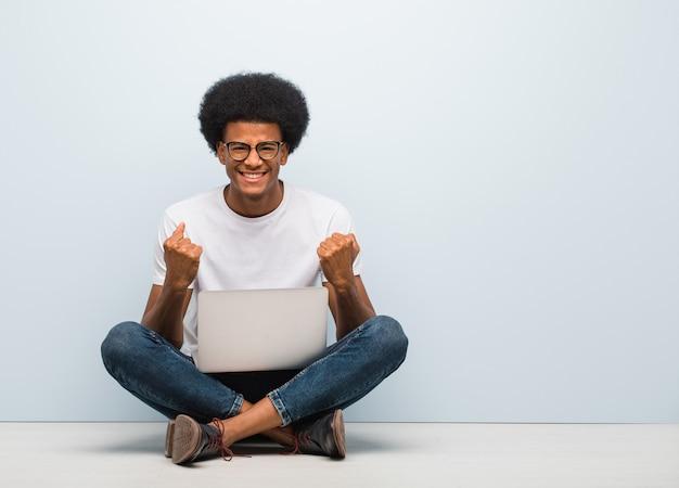 Giovane uomo di colore che si siede sul pavimento con un computer portatile sorpreso e scioccato