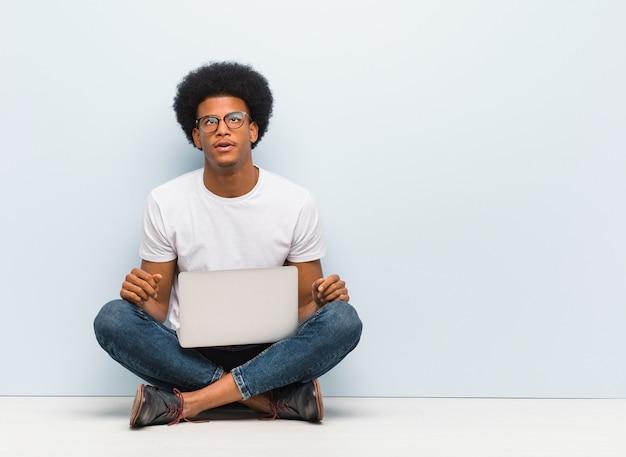 Giovane uomo di colore che si siede sul pavimento con un computer portatile stanco e annoiato