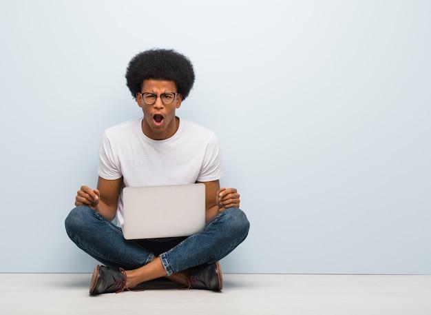 Giovane uomo di colore che si siede sul pavimento con un laptop che grida molto arrabbiato ed aggressivo