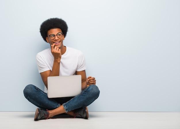 Giovane uomo di colore che si siede sul pavimento con un pensiero rilassato del computer portatile a qualcosa che esamina uno spazio della copia