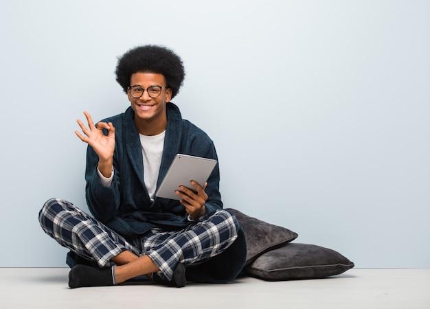 Giovane uomo di colore che si siede sulla sua casa e che tiene la sua compressa allegra e sicura che fa gesto giusto