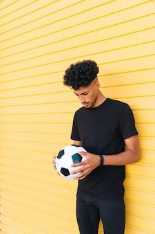 Giovane uomo di colore con la testa di abbassamento del pallone da calcio