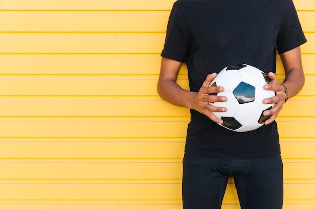 Giovane uomo di colore con pallone da calcio