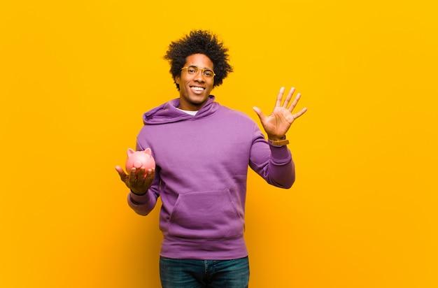 Giovane uomo di colore con un salvadanaio