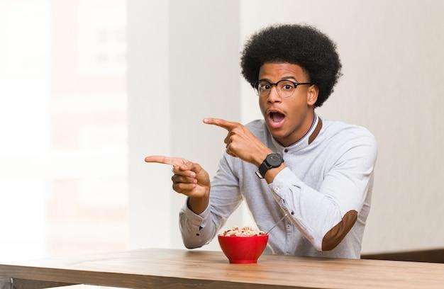 Giovane uomo di colore con una colazione che punta verso il lato con un dito