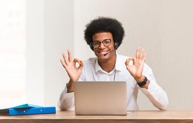 Giovane uomo di colore di telemarketer che esegue yoga