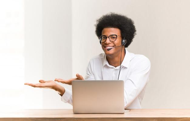 Giovane uomo di colore di telemarketer che tiene qualcosa con le mani