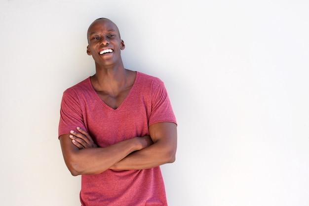 Giovane uomo di colore felice che sorride contro la parete bianca