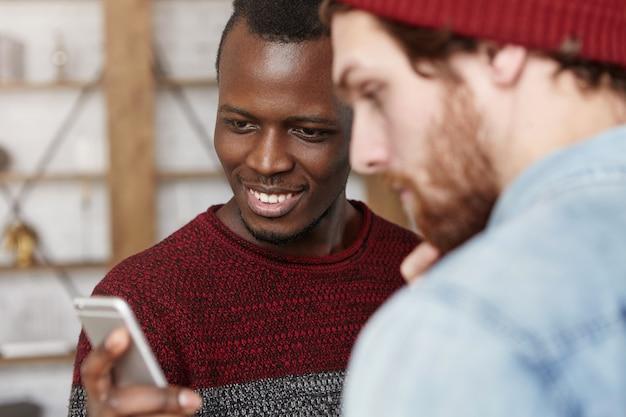 Giovane uomo di colore felice emozionante in maglione che mostra il suo amico bianco alla moda che ispira l'account del blog sui social network. due migliori amici maschi che utilizzano il telefono cellulare insieme al caffè. messa a fuoco selettiva