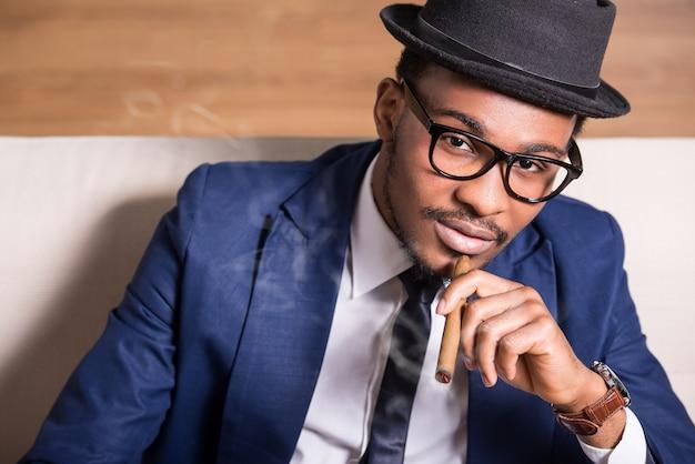 Giovane uomo di colore indossa abito e cappello, fumando un sigaro.