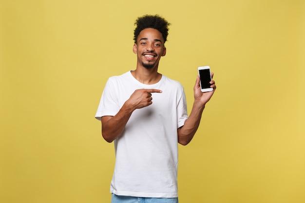 Giovane uomo di colore isolato su sfondo giallo, tenendo smartphone in bianco