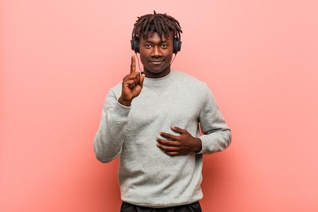Giovane uomo di colore rasta che ascolta la musica con le cuffie che mostrano numero uno con il dito.
