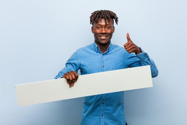 Giovane uomo di colore rasta che tiene un cartello che sorride e che alza pollice in su