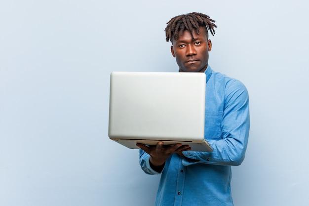 Giovane uomo di colore rasta in possesso di un computer portatile sorridente fiducioso con le braccia incrociate.