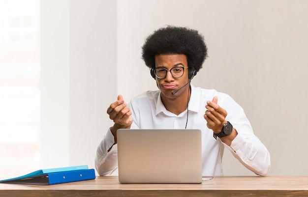 Giovane uomo di colore telemarketer che fa un gesto di bisogno