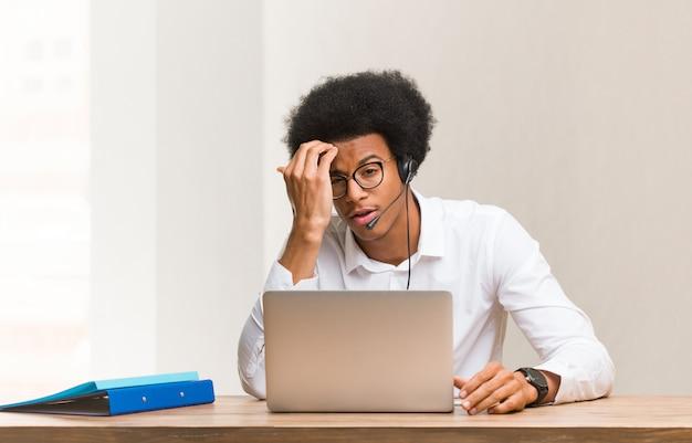 Giovane uomo di colore telemarketer preoccupato e sopraffatto