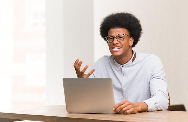 Giovane uomo di colore usando il suo laptop molto spaventato e impaurito