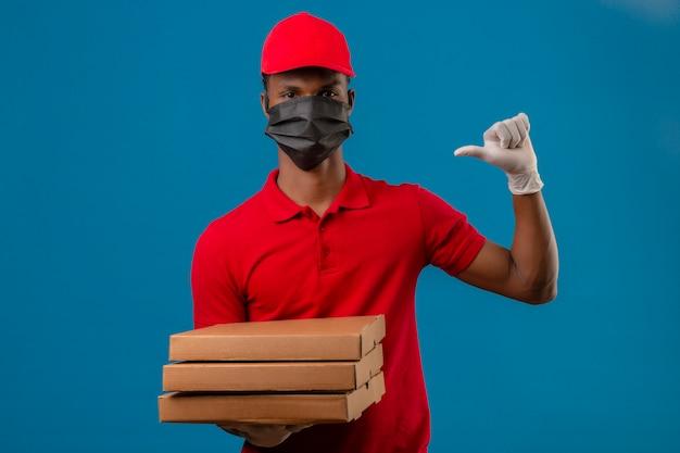 Giovane uomo di consegna afroamericano che indossa la polo rossa e il cappuccio in maschera protettiva e guanti in piedi con la pila di scatole per pizza che punta con il dito a se stesso su blu isolato