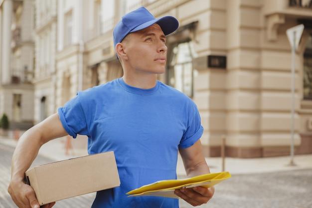 Giovane uomo di consegna allegro con scatola di cartone pacco per le strade della città