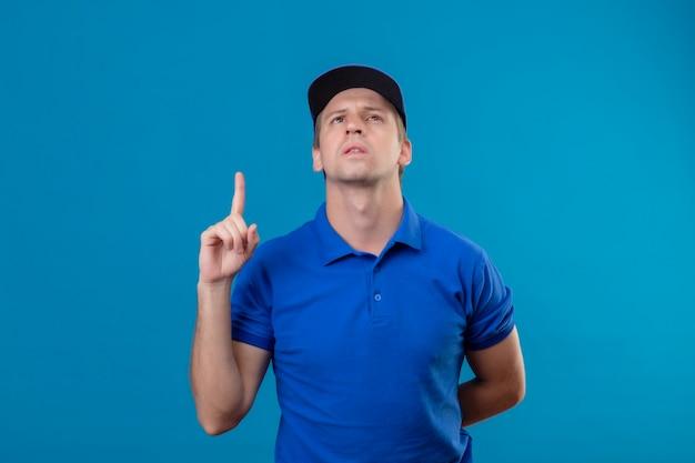 Giovane uomo di consegna bello in uniforme blu e cappuccio che osserva in su che indica il dito verso l'alto ricordando a se stesso di non dimenticare la cosa importante che sta sopra la parete blu