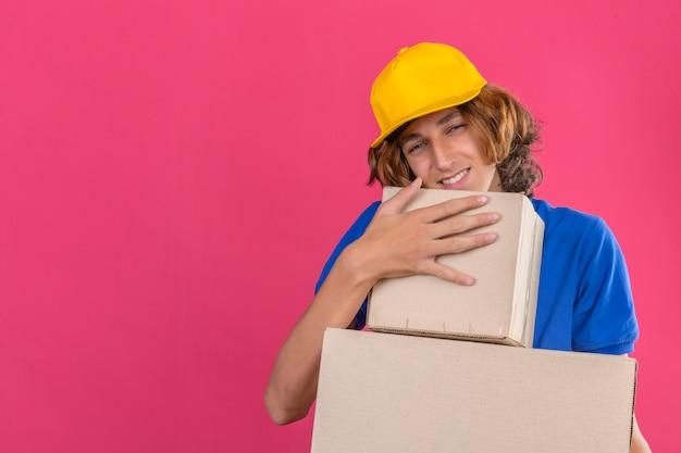 Giovane uomo di consegna che indossa la maglietta di polo blu e cappuccio giallo che tiene le scatole di cartone che sognano che abbracciano le scatole che sorridono con la faccia felice sopra fondo rosa isolato