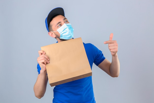 Giovane uomo di consegna che indossa la maglietta polo blu e cappuccio che indossa la maschera medica protettiva tenendo il pacchetto di carta con cibo da asporto che punta a questo pacchetto con il dito sorridente su backgrou bianco isolato
