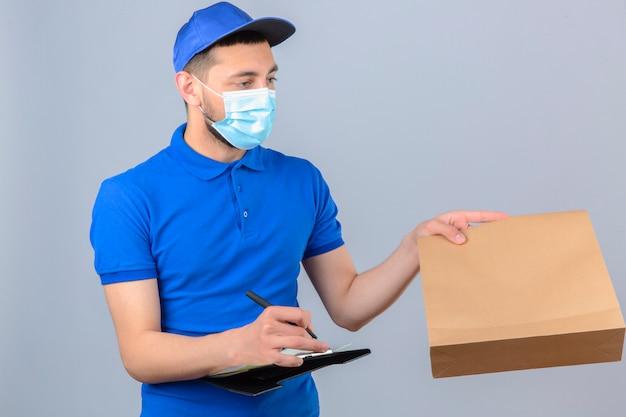 Giovane uomo di consegna che indossa la maglietta polo blu e cappuccio nella mascherina medica protettiva dando un pacchetto a un cliente e iscritto negli appunti su sfondo bianco isolato