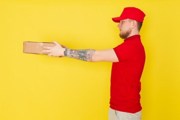 Giovane uomo di consegna in polo bianco rosso cappello rosso jeans in possesso di una scatola su giallo