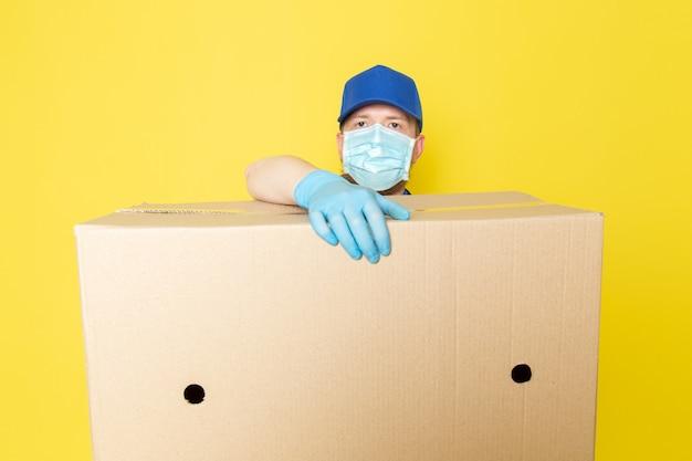 Giovane uomo di consegna in polo blu berretto blu jeans bianchi zaino in possesso di una scatola su giallo