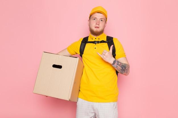 Giovane uomo di consegna in polo giallo berretto giallo jeans bianchi in possesso di una scatola sul rosa