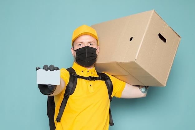 Giovane uomo di consegna in polo giallo berretto giallo jeans bianchi zaino e maschera sterile nera in possesso di una scatola su blu