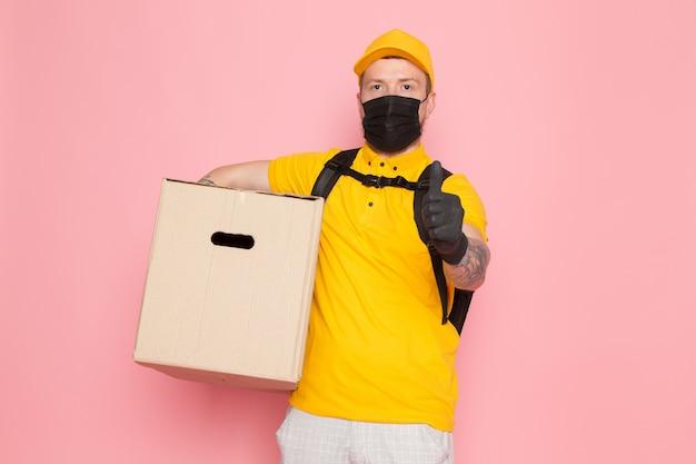 Giovane uomo di consegna in polo giallo berretto giallo zaino bianco jeans e maschera sterile nera con una scatola in rosa