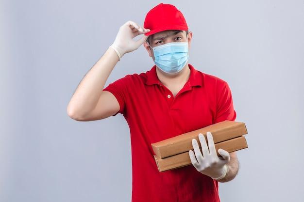 Giovane uomo di consegna in polo rossa e cappuccio in maschera medica tenendo scatole per pizza facendo il gesto di saluto toccando la sua camma con la mano con grave scettico sul viso e dispiacere