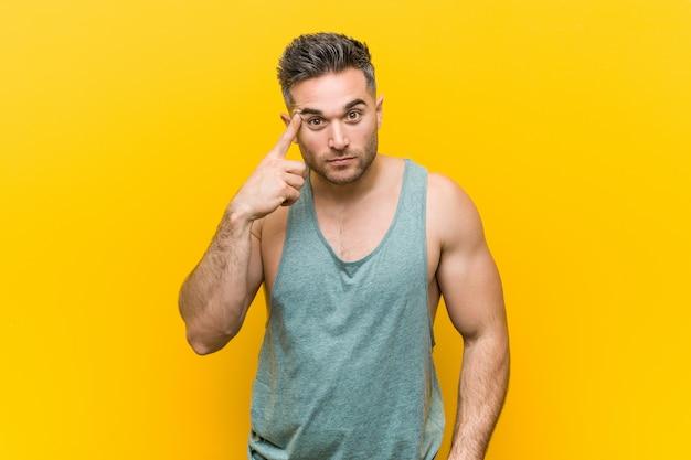 Giovane uomo di forma fisica che indica tempio con il dito, pensando