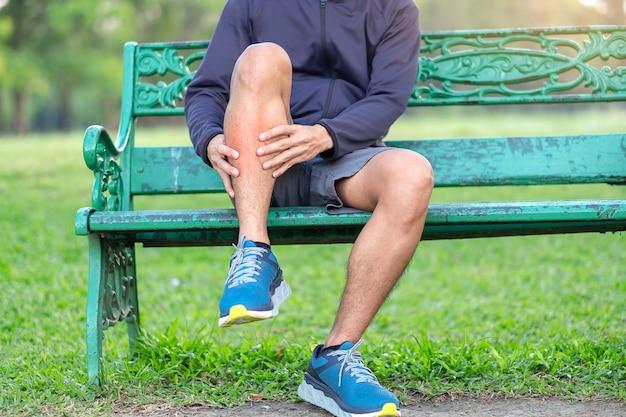 Giovane uomo di forma fisica che tiene la sua ferita della gamba di sport.