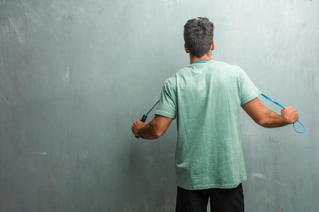 Giovane uomo di forma fisica contro una parete del grunge che mostra indietro, posante e aspettante, guardante indietro