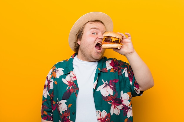 Giovane uomo di grandi dimensioni con un hamburger al formaggio contro la parete piatta