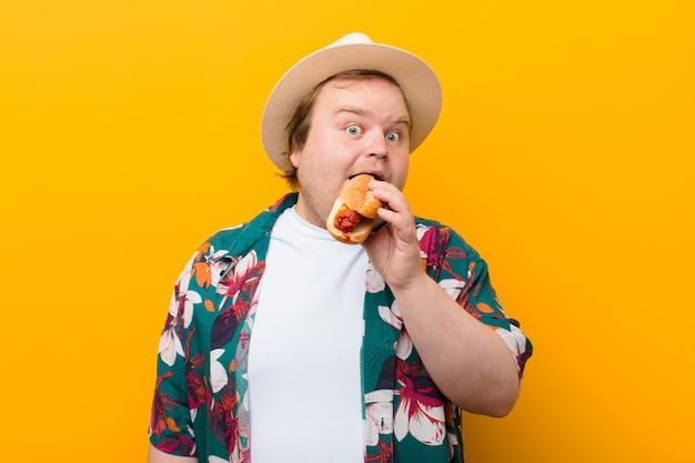 Giovane uomo di grandi dimensioni con un hot dog contro la parete piatta